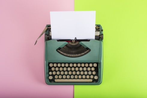 Vintage typewriter with paper sheet on pink and green background